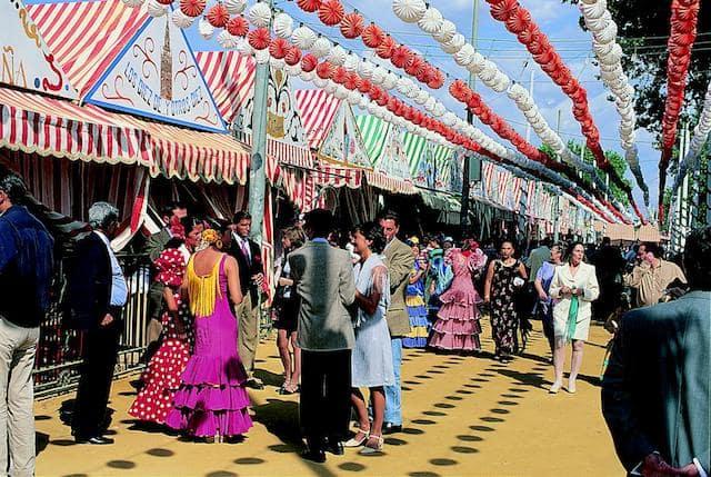 Casetas e pessoas com trajes na Feria de Sevilha